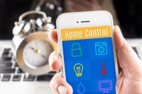 Hand holding smart phone with home control application with clock and computer at background, Smart home concept.